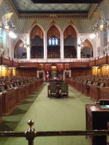 The House of Lords chamber in the Parliament Building.  The color green is dominant. The Senate has a similar chamber, where the color red is dominant