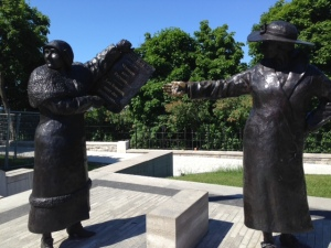Two of the women in the sculpture commemorating the court ruling - one holding up the front page of a newspaper to three other women in the sculpture