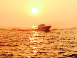 This is a boat coming into Grand Haven harbor at sunset