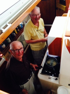 Dad and Tom cooking dinner on board - pan-fried fish, rice, and broccoli - what a feast!
