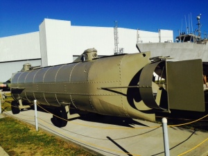 This is a replica of the Hunley, the first submarine ever to sink an enemy ship.  It was built in secrecy by the Confederacy in 1863-1864, and several crews drowned during attempts to deploy it. However, on February 17, 1864, it successfully planted an underwater charge on a union ship. The Hunley surfaced and sent a coded message of success to shore.  However, it then silently sank beneath the waves for reasons that have never been determined, drowning its 8 man crew. The Hunley was located and raised in recent years, and is on display in Charleston, South Carolina
