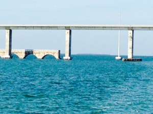 The original concrete-arch railroad bridge with the new highway bridge next to it. Each span of the old bridge has a section removed at the highest span of the new bridge to allow tall boats to pass through. Each remaining section of the old bridge is now used as a fishing pier.