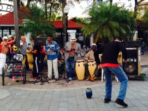 A Cuban band plays music while people dance in Dominos Park