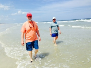 """Sol walking on the sand, in the salt & surf, and also in the sun! Dave is walking behind him, watching for sharks (another """"s"""" that he doesn't like...)."""