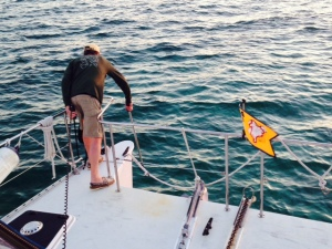 In the Bahamas, we always used a trip line with a float on the anchor so we could pull it up if it got snagged on a rock or coral or other obstruction on the seabed. Here Jim is pulling up the float on the trip line while the anchor is being raised.