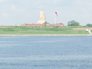 """Fort McHenry, as seen from the water while entering Baltimore Harbor. In the War of 1812, the British intended to burn Baltimore as their next target after having just burned Washington DC. However, they first had to capture Fort McHenry, which guarded the harbor. After 25 hours of bombardment from a fleet of battleships in the harbor, the fort held and the British withdrew. Francis Scott Key, having been captured earlier and imprisoned on a barge anchored in the harbor, awoke in """"dawn's early ligh"""" and saw the American flag still flying over the fort - inspired, he sat down and wrote """"The Star Spangled Banner""""."""