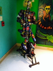 A man on a treadmill, built from old coffee cans -
