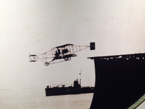 "A photo in the Naval Museum shows the first airplane to take off from the deck of a ship.  YIKES!  Thus Naval aviation was born in Hampton Roads at Norfolk in 1910 when this pusher biplane flew off a ""flight deck"" constructed on the USS Birmingham. The flight to Willoughby Island took just five minutes, but it success signaled the advent of aircraft carriers."